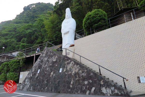 Photo of strange position serious bust sculpture at the foot of strange position buddha statue